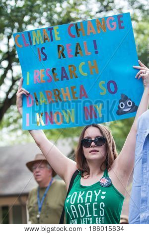 ATLANTA, GA - APRIL 22:  A young woman holds up a funny sign about climate change as she takes part in the Atlanta March for Science near Candler Park in Atlanta GA on Earth Day on April 22 2017.