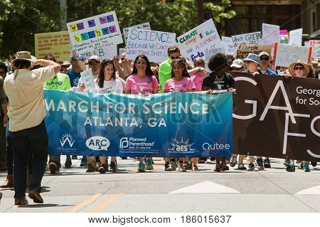 ATLANTA, GA - APRIL 22:  People carry the Atlanta March for Science banner as thousands line up behind to begin the march at Candler Park on Earth Day in Atlanta GA on April 22 2017.