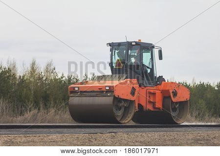 Asphalt compactor - road rollers at asphalt pavement works - construction of the highway, telephoto