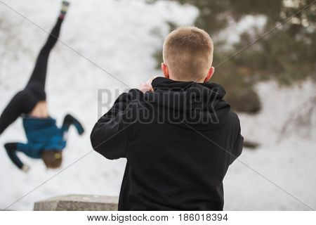 Teenager take a photo for acrobatic jump girl in winter city park - parkour concept, telephoto