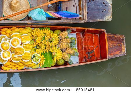Long-tail boat with fruits on the floating market Damnoen Saduak floating market in Ratchaburi near Bangkok Thailand