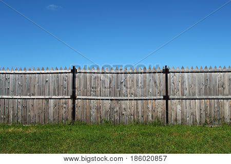 Wooden fence. Summer. Daytime. Grass. Unclouded sky.
