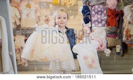 Shopping for girls - blonde little girl showing new purchases in store of child's clothes, telephoto