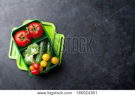 Lunch box with vegetables. Kids healthy take away food box. Top view on blackboard with space for your text