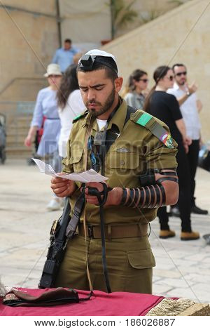 JERUSALEM, ISRAEL - APRIL 30, 2017: Israeli soldier prays by the Western Wall at the Old City of Jerusalem.