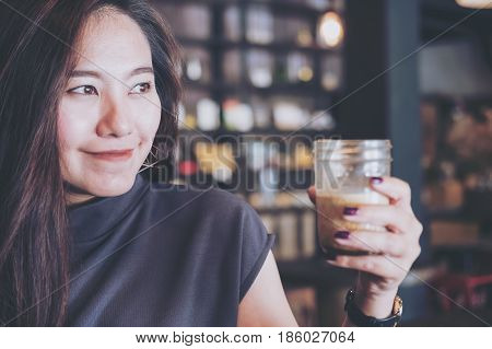 Closeup image of a beautiful Asian woman holding and drinking hot coffee with feeling good in modern loft cafe