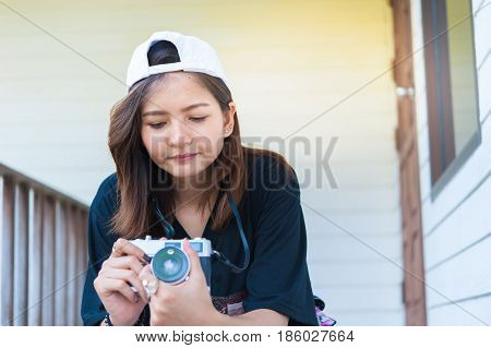 Hipster woman taking photos with retro film camera on wooden floorof city parkbeautiful girl photographed in the old camera