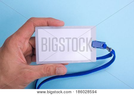 lanyard and badge blank space for text with blue ribbon the man is holding in his hand. Blue or blue background
