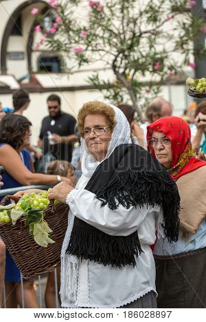 FUNCHAL PORTUGAL - SEPTEMBER 4 2016: women in traditional costume carry the basket of grapes durnig historical and ethnographic parade of Madeira Wine Festival in Funchal. Madeira Portugall