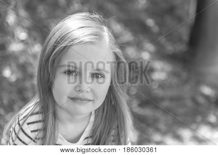 Beautiful little girl with long pretty light hair, smiling shyly, close portrait, gray photo