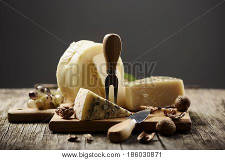 Various cheese, walnuts and grape on rustic wooden table with dark background