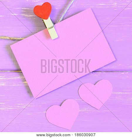 Clothespin hanging with pink empty paper card. Two pink paper hearts on lilac wooden background with copy space for text. Wedding, Valentines day, birthday background, card