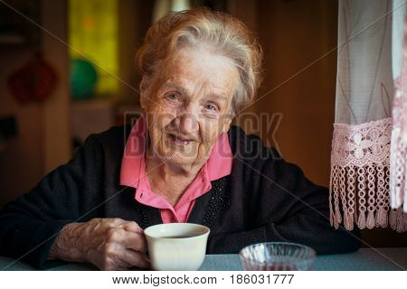 Elderly retired woman drinking tea in his house.