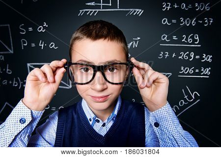Funny smart boy in formal suit and glasses over school blackboard. Educational concept.