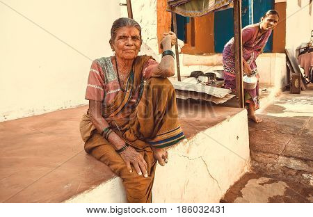 BADAMI, INDIA - FEB 8, 2017: Elderly woman in traditional dress sitting near rural home in indian village on February 8, 2017. Population of Karnataka state is 62000000 people