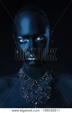 Body painting project. Portrait of a beautiful young woman with perfect black skin and silver glitter lips wearing beautiful necklace. Cosmetics and make-up. Jewelry and bijouterie.