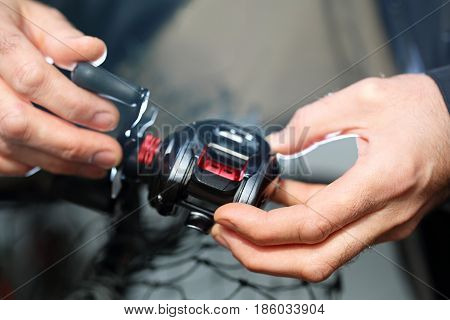Fishing reel. The man holds an fishing reel in his hands