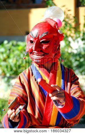Atsara (Joker) wearing red traditional Bhutanese dress entertaining people in Mask Dance Festival in Bhutan