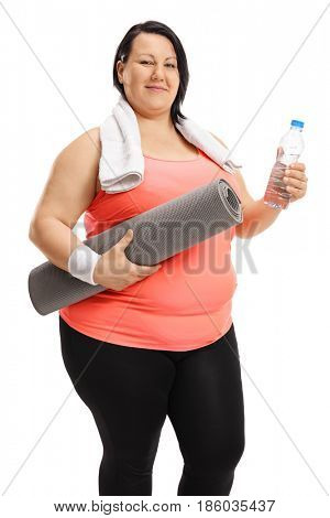 Overweight woman holding an exercising mat and a bottle of water isolated on white background