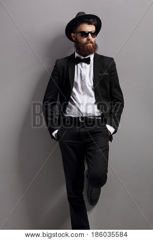 Bearded guy with sunglasses and a bow tie leaning against a gray wall