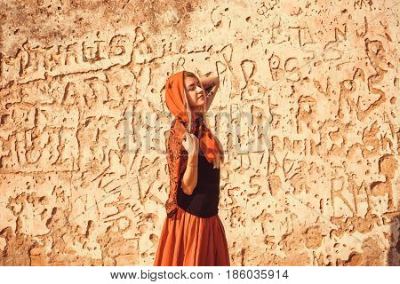 Romantic girl in red clothes dreaming at the wall of house, with signs of modern graffiti