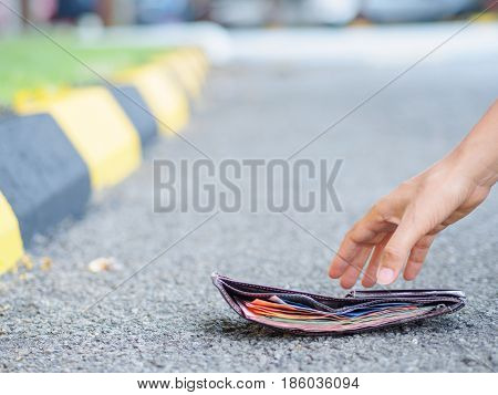 Close-up Of A Woman Picking Up Fallen Wallet On road side