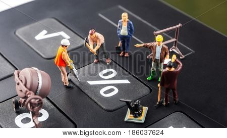 constantly changing interest rates / fixing the problem concept closeup of miniature figurine of workers repairing percentage button on a big black calculator