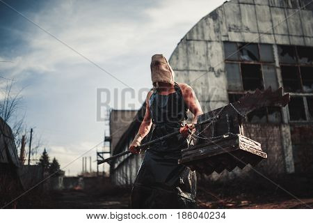 Mutant monster with weapon in form of hammer saw and an ax. Imagination. Mutant with sack on his head.