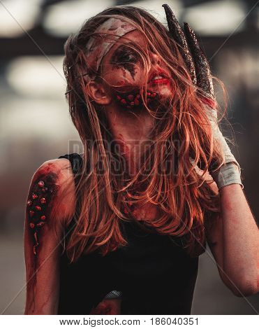 Mutant girl portrait in wounds and ulcers with nails in her head and claws instead of fingers. On her head and hands is bandage.