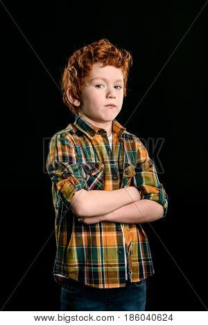 Portrait Of Adorable Redhead Boy With Crossed Arms Looking At Camera Isolated On Black