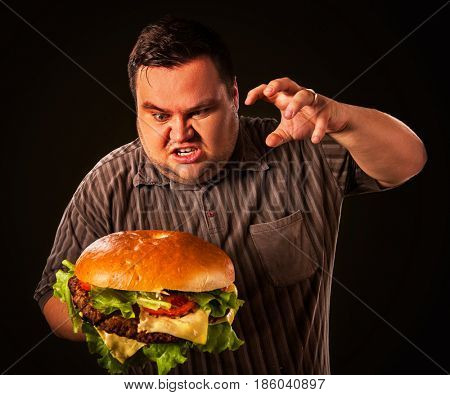 Diet failure of fat man eating fast food hamberger. Aggressive overweight person who spoiled healthy food by eating huge hamburger. Junk meal leads to obesity. End of diet.
