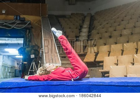 The future circus artist. Female gymnast doing stretching at the barrier of the arena in the circus.