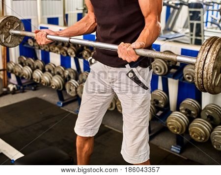 Man dumbell workout in gym. Muscle male working with dumbbells his body at gym. Top view of handsome sportsman. Doing sports to maintain health in gym. Student decided to engage in fitness.