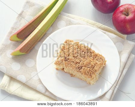 Rhubarb and apple crumble pie. Homemade biscuit cake decorated with crumbs and wet rhubarb stems. Summer fruits cake. Top view.