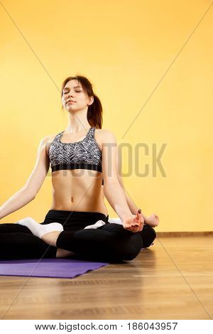 Two sportswomen sitting in lotus position at gym