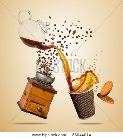 Cup with splashing coffee and grinder separated on brown background. Hot drink with splash, beverages and refreshment.