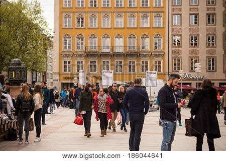 Munich,Germany-May 9,2017:Tourists and locals walk on Marienplatz with an Information Stand from the PEGIDA movement in the background