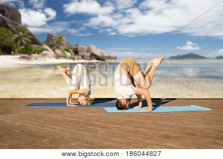fitness, sport, yoga, people and healthy lifestyle concept - couple making headstand outdoors over tropical beach background