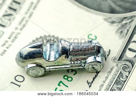 Little Car Made Of Chrome Is Laying On One Dollar Banknote