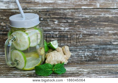 Detox infused water with lime lemons and ginger in mason jar on wooden background. Delicious refreshing summer drink. Healthy lifestyle detox diet loss weight concept.Space for text.