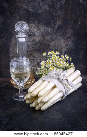 Row white Asparagus with wine and flower as close-up on an old rustic metal sheet