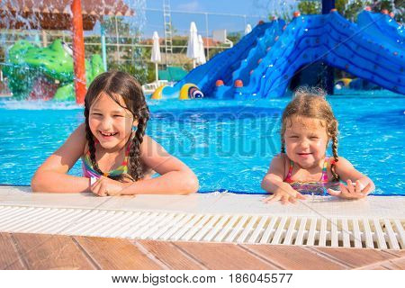 Funny laughing kids in the pool. Summer vacation family vacation concept.