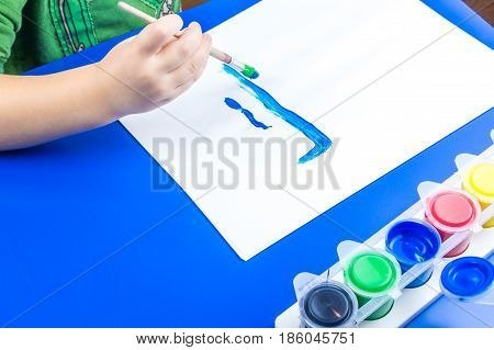 Child Is Painting A Picture With Tempera Paints On Blue Table