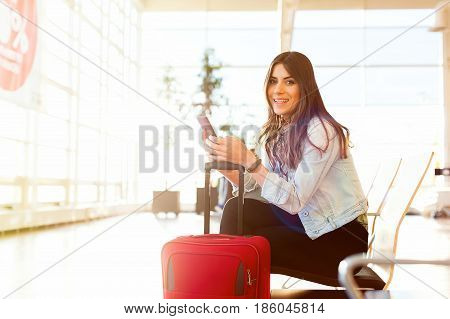 Casual young woman sitting, using her cell phone while waiting to board a plane at the airport terminal waiting room.