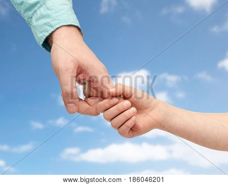 family, childhood, fatherhood and people concept - father and child holding hands over blue sky and clouds background