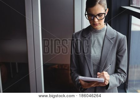 Counselor writing on the notepad in office