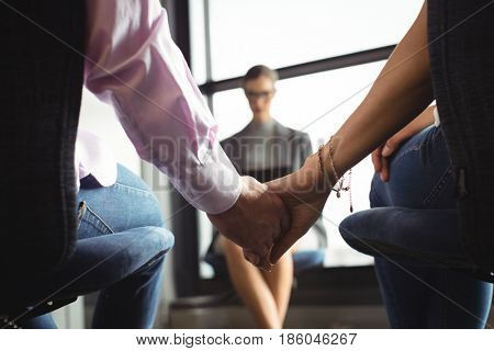 Mid section of couple holding hands with marriage counselor