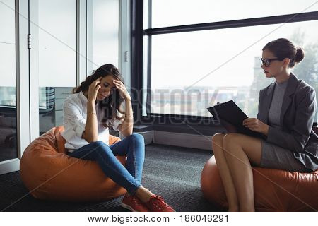 Unhappy woman consulting counselor during therapy