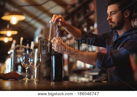 Male bar tender opening a bottle of wine at bar counter