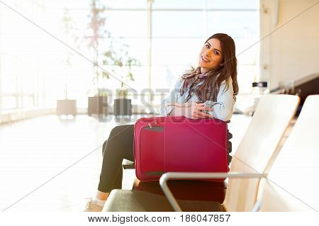 Woman smiling, waiting her flight at airport terminal, sitting, in waiting room with her trolley bag.